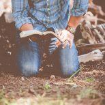 homme à genoux avec une Bible ouverte